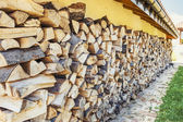 Wooden logs stacked by a house — Stock Photo