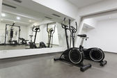 Elliptical trainer and bike in exercise room — Stok fotoğraf