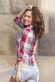 Beautiful young woman in denim hot pants and plaid shirt — Stock Photo