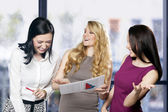 Three women at workplace joking and laughing — Stock Photo