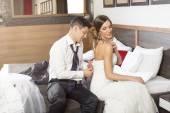 Happy newlyweds in hotel room - groom undressing bride — Stock Photo