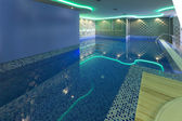 Indoors pool with colorful lights at spa center — Stockfoto