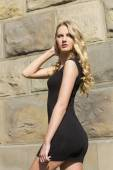 Young woman posing outdoors in short black dress — Stockfoto