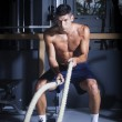 Muscular man in gym with battle ropes — Stock Photo #77048049