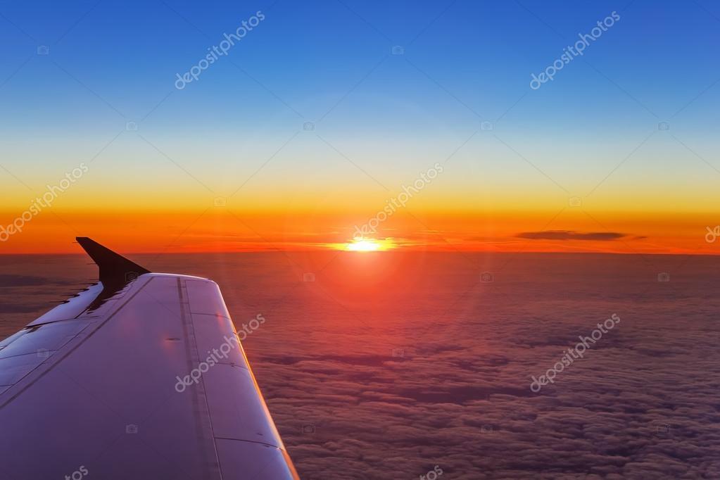日没の背景で雲の上の飛行中の飛行機の翼– ストック画像