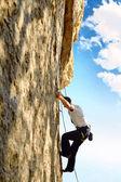 Rock climber climbing up a cliff — Foto de Stock