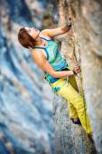 Rock climber climbing up a cliff — Stock Photo