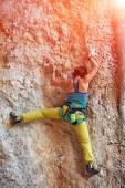 Rock climber climbing up a cliff — Stock Photo
