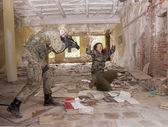 Female hostage and soldier with gun — Stock Photo