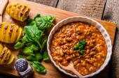 Spicy cowboy beans with hassleback potatoe with herbs — Stock Photo