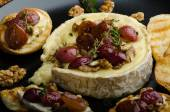 Brie cheese baked with nuts and grapes — Stock Photo