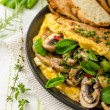 Omelet with mushrooms, lambs lettuce, herbs and chilli — Stock Photo #78312394