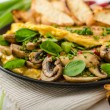 Omelet with mushrooms, lambs lettuce, herbs and chilli — Stock Photo #78312446