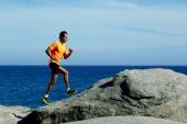 Middle age man at workout outdoors jogging along the sea — Stock Photo