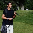 Handsome wealthy man in polo t-shirt standing on golf course — Stock Photo #56581875