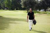 Golf player carrying his bag and walking on golf course — Stock Photo