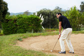 Man in sports clothing playing golf while standing golf sand — Stock Photo