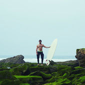 Professional surfer in black wetsuit standing on moss rocks — Stock Photo