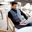 Handsome hipster man working with his laptop on the beautiful restaurant, work everywhere — Stock Photo #56639935