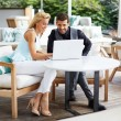 Business team of two successful people sitting outdoors in lounge terrace and planning work, businessman and businesswoman meeting in modern cafe, business partners having working with computer — Stock Photo #56639963
