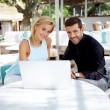 Business team of two successful people sitting outdoors in lounge terrace and planning work, businessman and businesswoman meeting in modern cafe, business partners having working with computer — Stock Photo #56640021