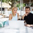 Business team of two successful people sitting outdoors in lounge terrace and planning work, businessman and businesswoman meeting in modern cafe, business partners having working with computer — Stock Photo #56640025