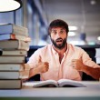 Surprise emotion face of male student sitting at a table in the library — Stockfoto #56646557
