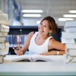 Asian student girl sitting at university library desk behind stack of book — Stock Photo #56646577