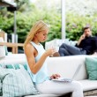 Beautiful blonde hair woman drinking coffee while using compute — Stock Photo #56646907