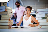 Frustrated college student sitting at the desk with huge pile of study book in university library — Stock Photo