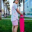 Young hipster man standing on the grass holding his longboard, stylish teenager man stand in california beach palm trees park looking away, leisure time at holidays, urban culture and youth — Stock Photo #60359815