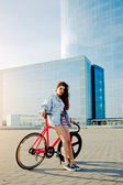 Attractive young woman win fixed gear bike posing outdoors with beautiful skyscraper on background, pretty young brown haired woman standing with her modern pink bicycle in city, stylish hipster girl — Stock Photo