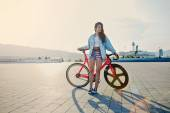 Pretty young brown haired woman standing with her modern pink bicycle at sunset, stylish hipster girl, attractive young woman win fixed gear bike posing outdoors with soft sunset light on background — Stock Photo