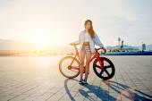 Attractive young woman win fixed gear bike posing outdoors with soft sunset light on background, pretty young brown haired woman standing with her modern pink bicycle at sunset, stylish hipster woman — Stock Photo