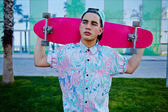 Young stylish man in bright summer clothes standing with pink long-board on beautiful glass background with reflected palm trees, cool teenager holding his long board looking away prank — Stock Photo