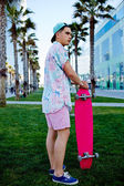 Young hipster man standing on the grass holding his longboard, stylish teenager man stand in california beach palm trees park looking away, leisure time at holidays, urban culture and youth — Stock Photo