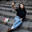 Pretty tourist girl taking a self portrait with smart phone in Barcelona, hipster girl photographing herself with phone, laughing student girl taking a self portrait with smart phone sitting on steps — Stock Photo #60360341