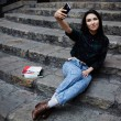 Young charming girl smiling while taking a self-ie outdoors,smiling student girl making a self portrait with smart phone sitting on steps, beautiful young hipster girl photographing herself with phone — Stock Photo #60360349