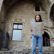 Beautiful tourist woman on vacation with a map in antique gothic city,young traveler girl searching right direction on city map, pretty young female tourist studying a map standing in gothic quarter — Stock Photo #60360413
