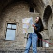 Beautiful tourist woman on vacation with a map in antique gothic city,young traveler girl searching right direction on city map, pretty young female tourist studying a map standing in gothic quarter — Foto Stock #60360415