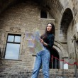 Attractive tourist girl on vacation with a map in antique gothic city, charming tourist woman studying a map standing in gothic quarter, young female traveler searching right direction on city map — Stock Photo #60360455