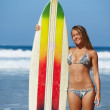Attractive woman surfer standing with surfboard at ocean seashore, beautiful bikini model on summer vacation engage water sports, at sunny day teenager girl in swimsuit holding her surfboard — Stock Photo #60360769