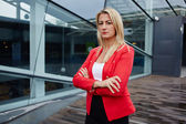 Portrait of a confident businesswoman standing against skyscraper office building, professional businesswoman with arms crossed, successful business woman looking confident — Stock Photo