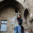 Charming tourist girl holding city map in the hands smiling, beautiful girl studying city map standing in gothic quarter in Barcelona, young tourist woman on vacation with a map in gothic quarter — Stock Photo #60464181