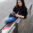 Young asian race woman read the book sitting on wooden bench, charming student girl concentrated reading some book outdoors, stylish tourist girl resting after long walk in new country — Stock Photo #60465621