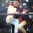 Happy stylish friends having coffee together, laughing young couple in cafe, having a great time together,view through cafe window, portrait of young couple in love at a coffee shop, people having fun — Stock Photo #60460007