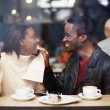 Portrait of young couple in love at a coffee shop, boyfriend wiping her mouth with a napkin at breakfast, romantic couple having fun together, two friends smiling sitting in cafe — Stock Photo #60460009
