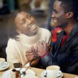Laughing young couple in cafe, having a great time together, view through cafe window, romantic couple having fun together, best friends smiling sitting in cafe, view through cafe window — Stock Photo #60460101