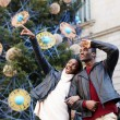 Laughing couple on christmas vacation walking in the city, beautiful woman pointing with he finger something interesting, romantic couple walk on christmas tree background on big square — Stock Photo #60460245