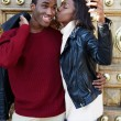 Stylish couple having fun making self portrait picture on digital camera of mobile phone, woman kissing boyfriend on the cheek photographing themselves with smartphone, couple in love on san valentine — Stock Photo #60460331